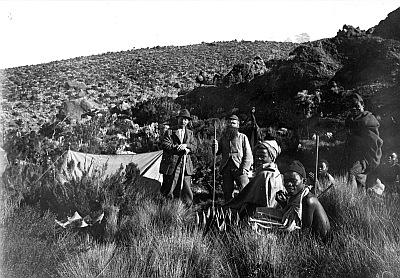 Meyer, Hans: 1886/1898, Der deutsche Geograph Hans Meyer und Pater Rohmer mit einheimischen Trägern vor ihrem Zelt am Südosthang des Kibo im Kilimandscharo-Massiv. Blick zum Mawenzi