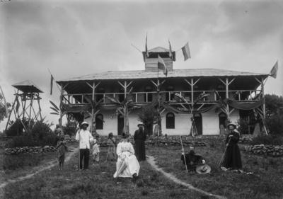 Meyer, Hans: 1886/1898, Gruppenbildnis vor dem Stationsgebäude der Deutsch-Ostafrikanischen Gesellschaft (DOAG) in Kibosho mit Amely Johannes (mittig sitzend) und Pater Rohmer (mittig stehend mit Hut).
