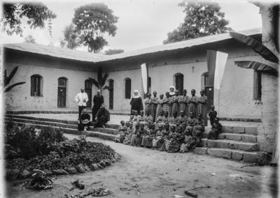 Meyer, Hans: 1886/1898, Gruppenbildnis vor einer Schule der Katholischen Mission, mit Forschungsreisendem, Laienbrüdern, Trappistinnen und Schülerinnen sowie Pater Rohmer (rechts hinter den Sitzenden)