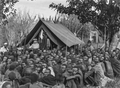Meyer, Hans: 1886/1898, Versammlung mit Männern der Chagga und Hauptmann Kurt Johannes, der vor einem Zelt an einem Tisch sitzt