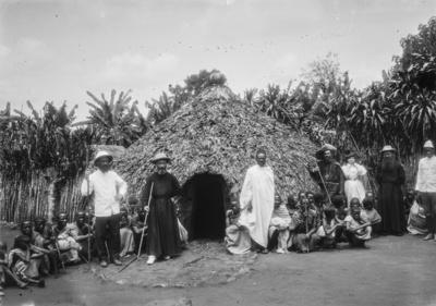 Meyer, Hans: 1886/1898, Gruppenbildnis von Männern, Frauen und Kindern der Chagga, Forschungsreisenden und Missionaren vor einer Hütte. Darunter Amely Johannes (dritte von rechts) und Pater Rohmer