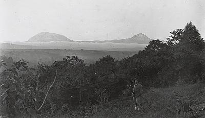 1887 - Meyer, Hans: Kilimandscharo. Blick auf Kibo und Mawensi, Ansicht über Bergregenwald von einem Hügel bei Moshi (ca. 1000 m) von Süden. Im Vordergrund Hans Meyer, Sommer 1887